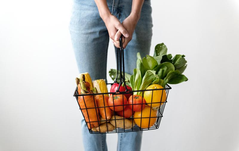 Woman holding grocery basket.