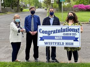 Photo of WHS 12th grader posing with teachers and lawn sign