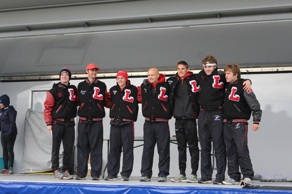 Boys in athletic warmups standing in a line on a podium