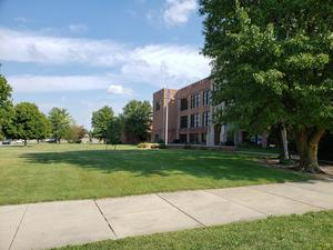 picture of grass, trees, bushes in front of the High School