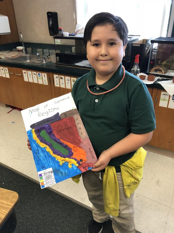 A student stands proudly with his finished map