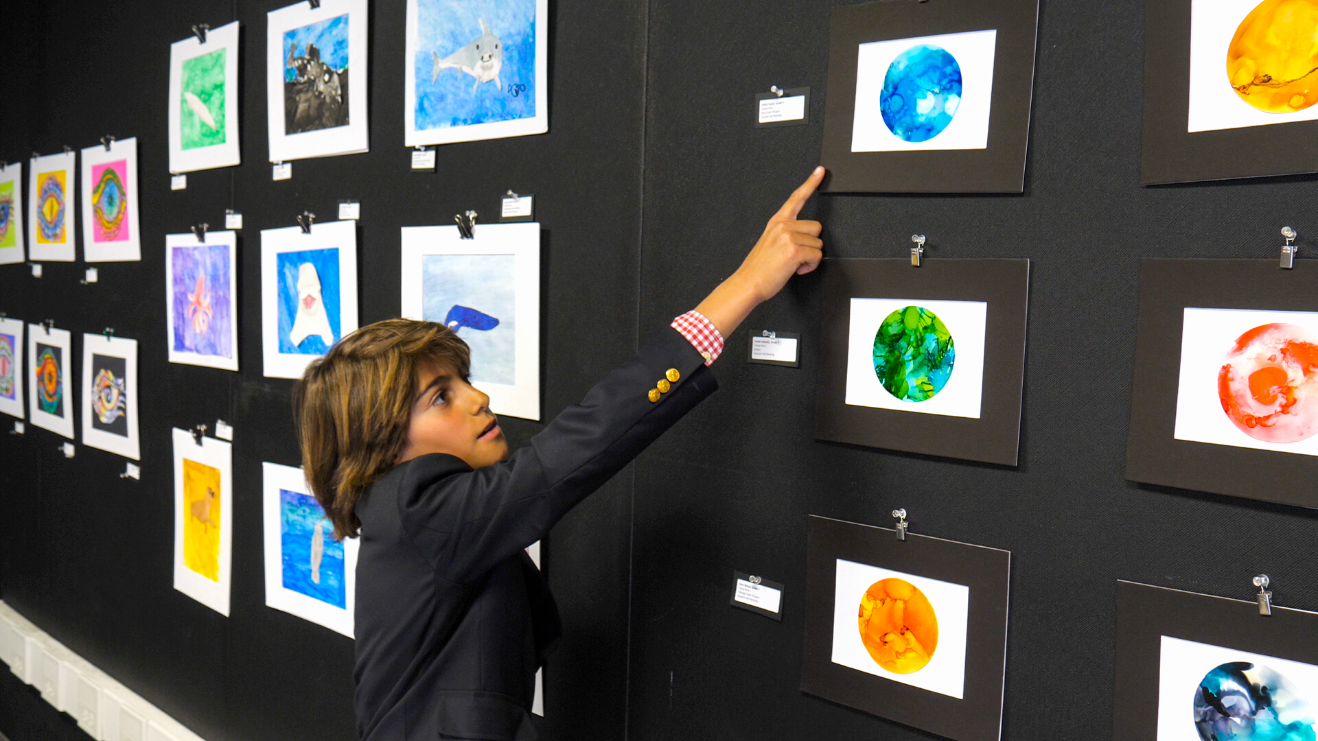 Renaissance 6th grade student showing off work at the all-school art show.