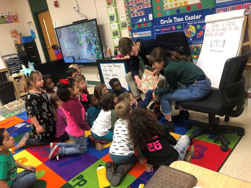 two teens read to group of pre-k students