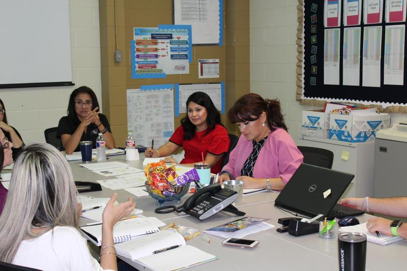 Administrators and teachers attending a grade level meeting.