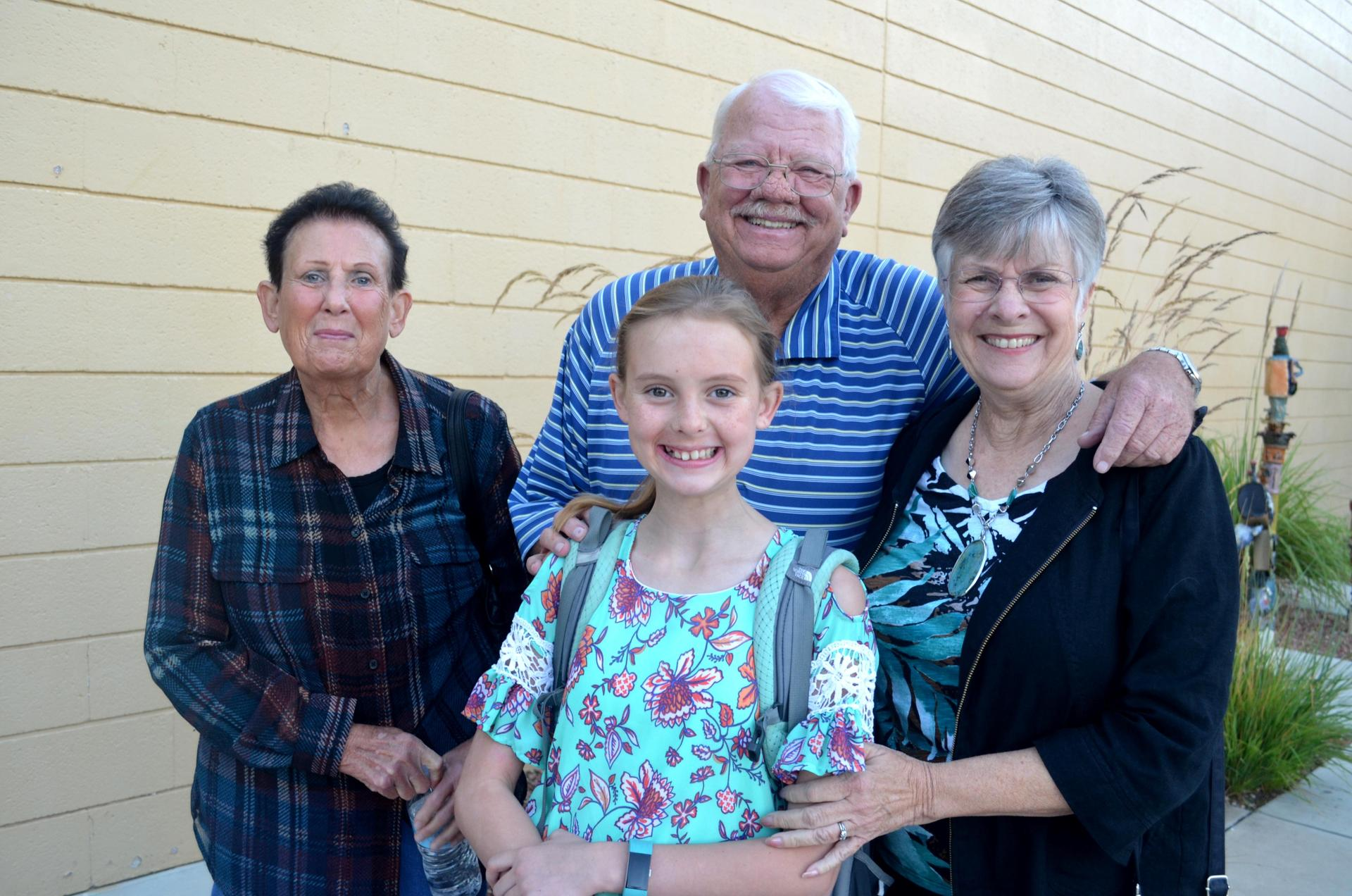 Students and grandparents smile at camera