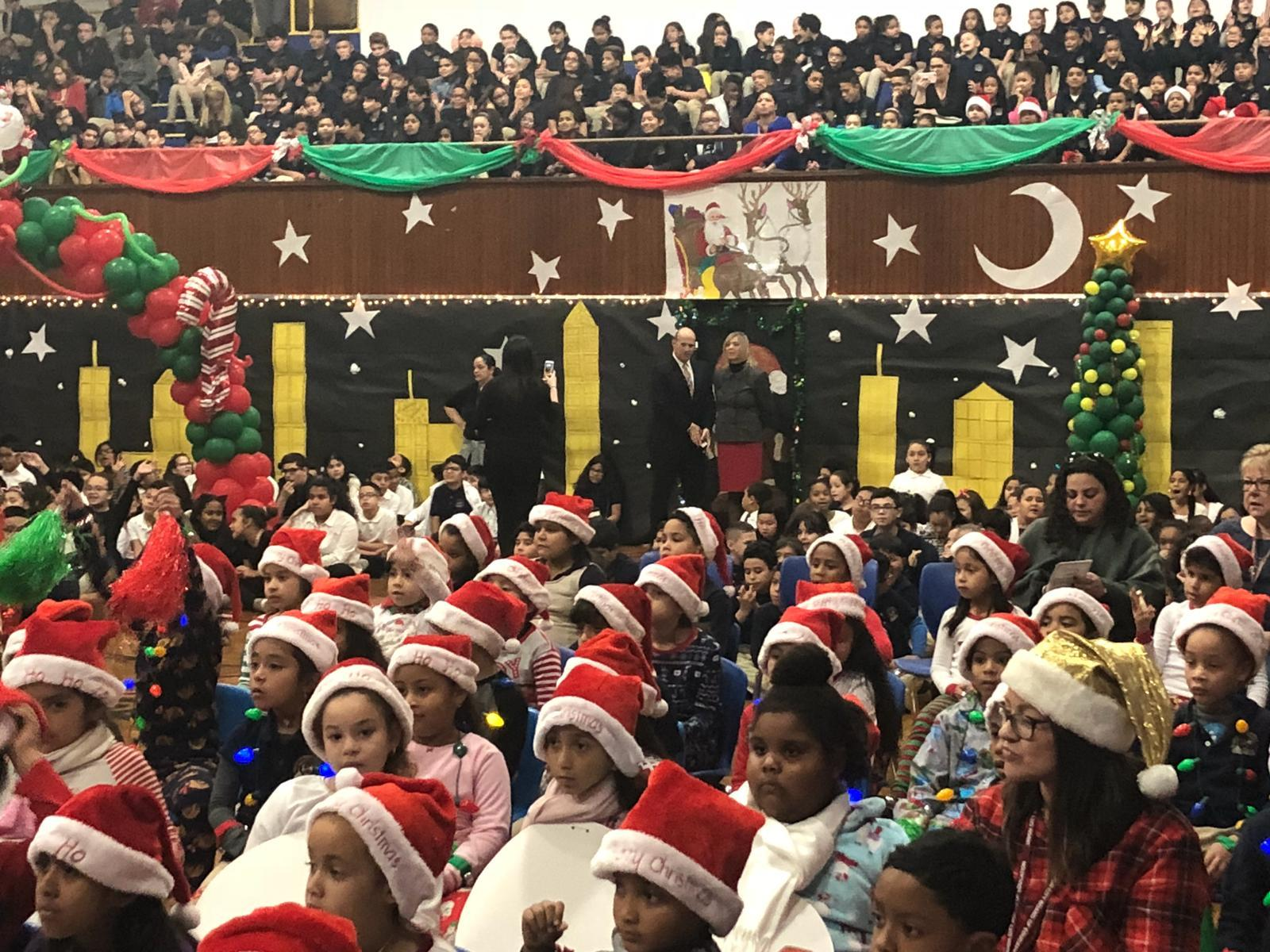 a crowd of young children wearing santa hats as the older children are sitting in the stands of the auditorium