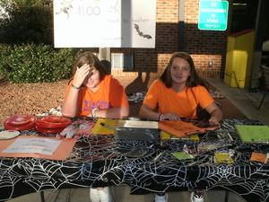 2 girls volunteer to help at the front tables.