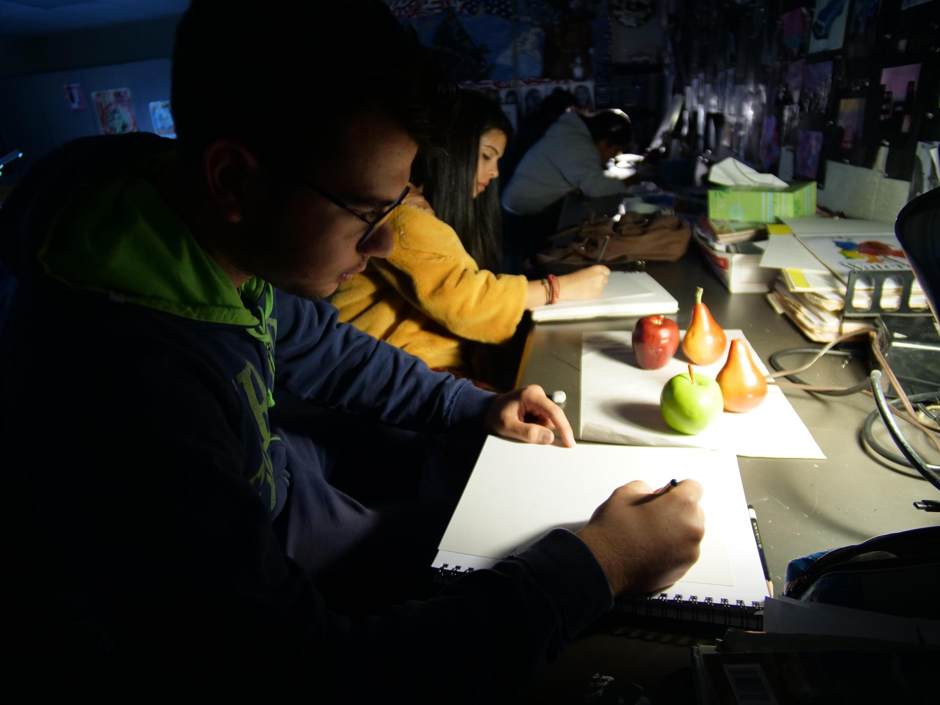 Art student works on shading skills in darkened classroom.