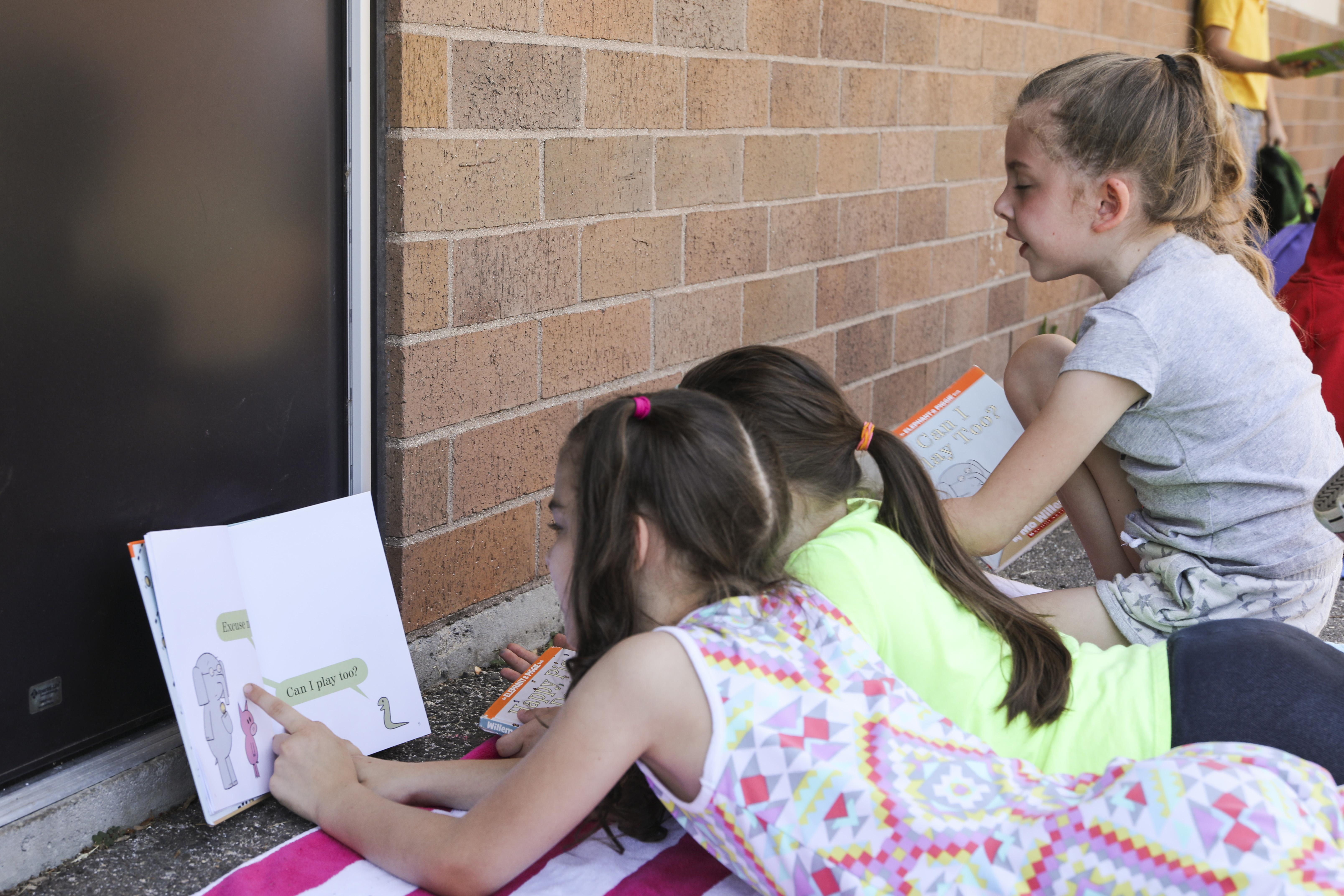 Three Maple Hill girls reading outside