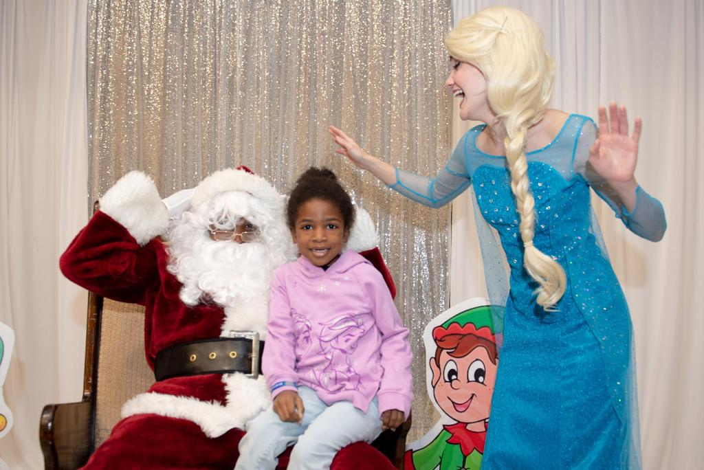 """Elsa from """"Frozen"""" spreads her arms as she looks at a girl who's visiting with Santa"""