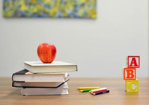 Books and an apple on a desk.