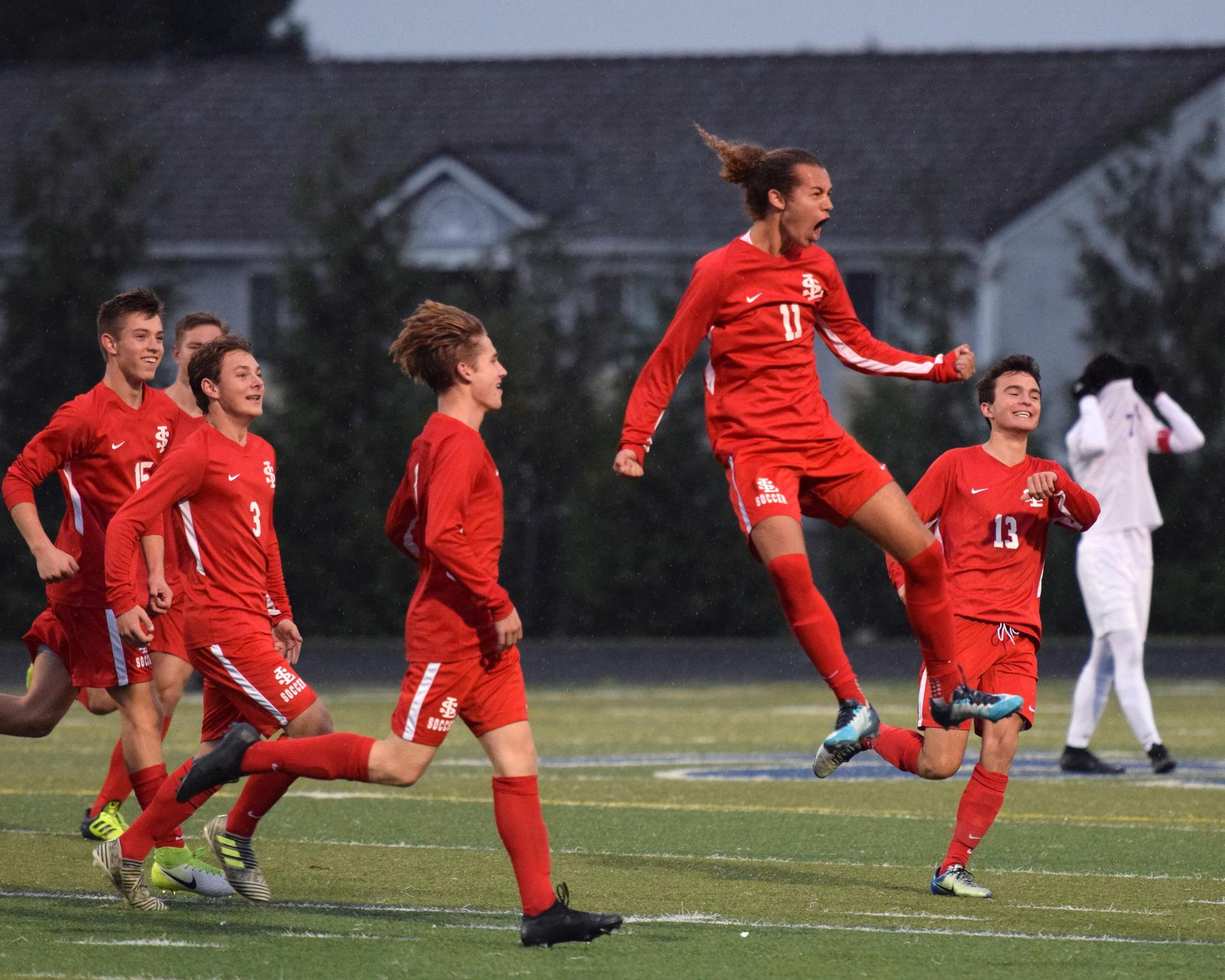 soccer players celebrate a goal and jump in the air