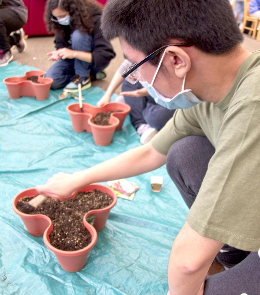 Students planting on a tarp on the floor