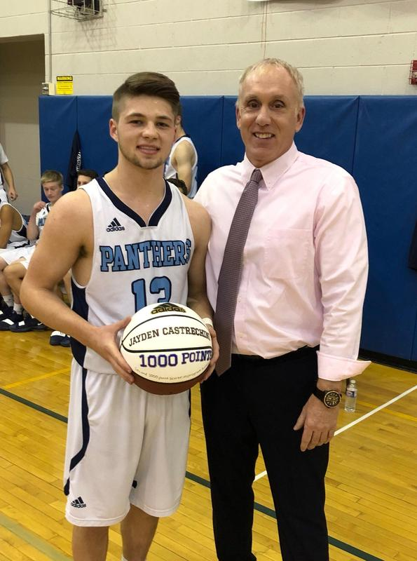 After reaching varsity career milestone of 1,000 points, Gananda senior, Jayden Castrechini, poses with Coach Thomson to celebrate.