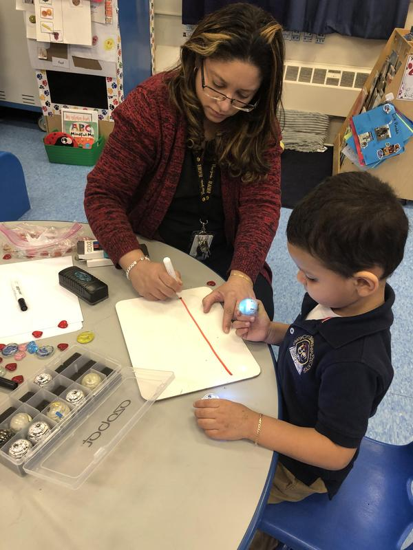 Ms. Ortiz drawing a red line with a boy students on tablet