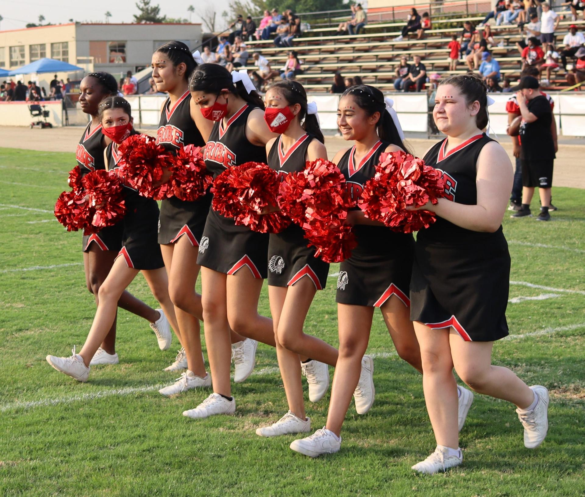 JV girls cheering at the football game against Lemoore