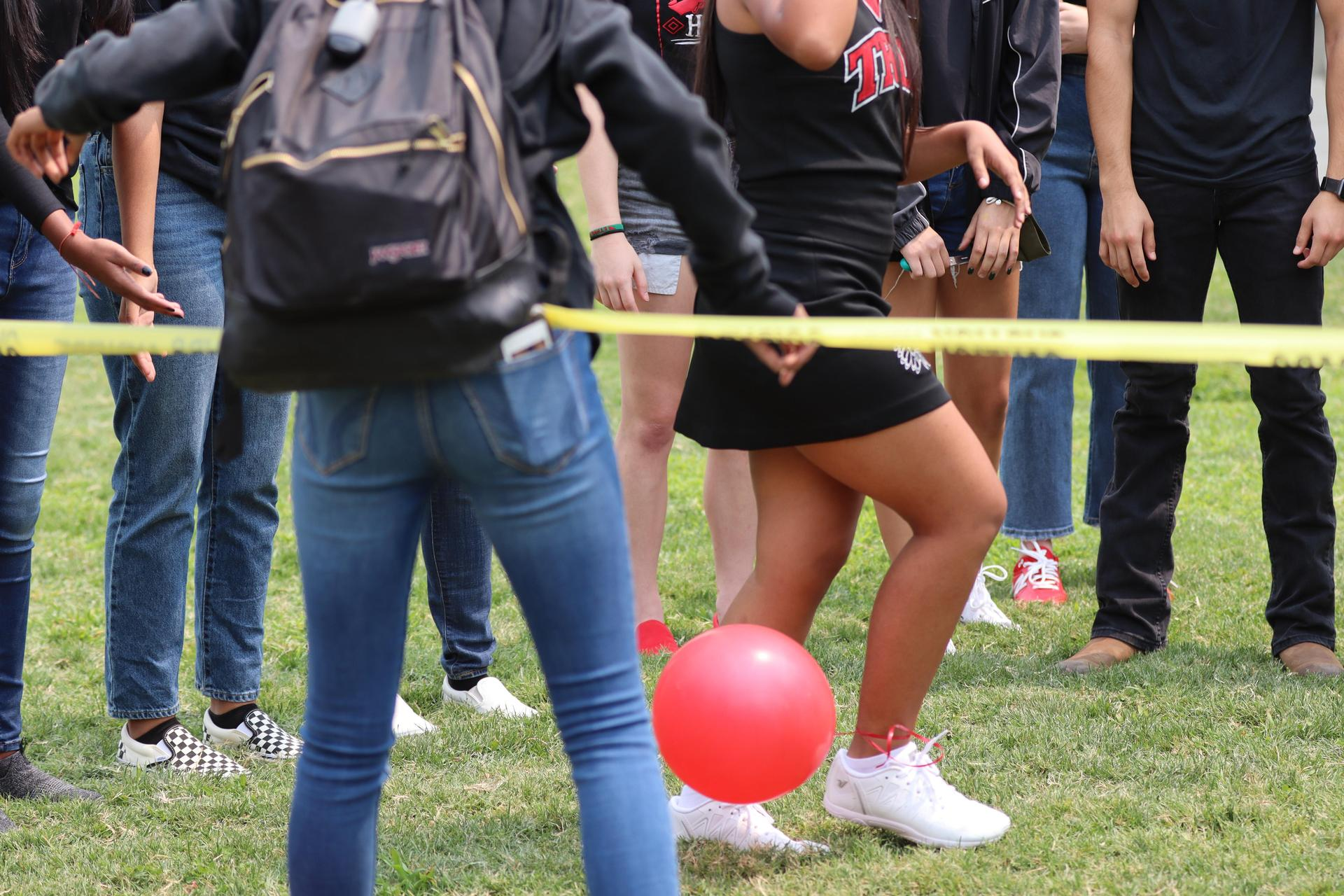 students popping the balloons tied to each other's ankles