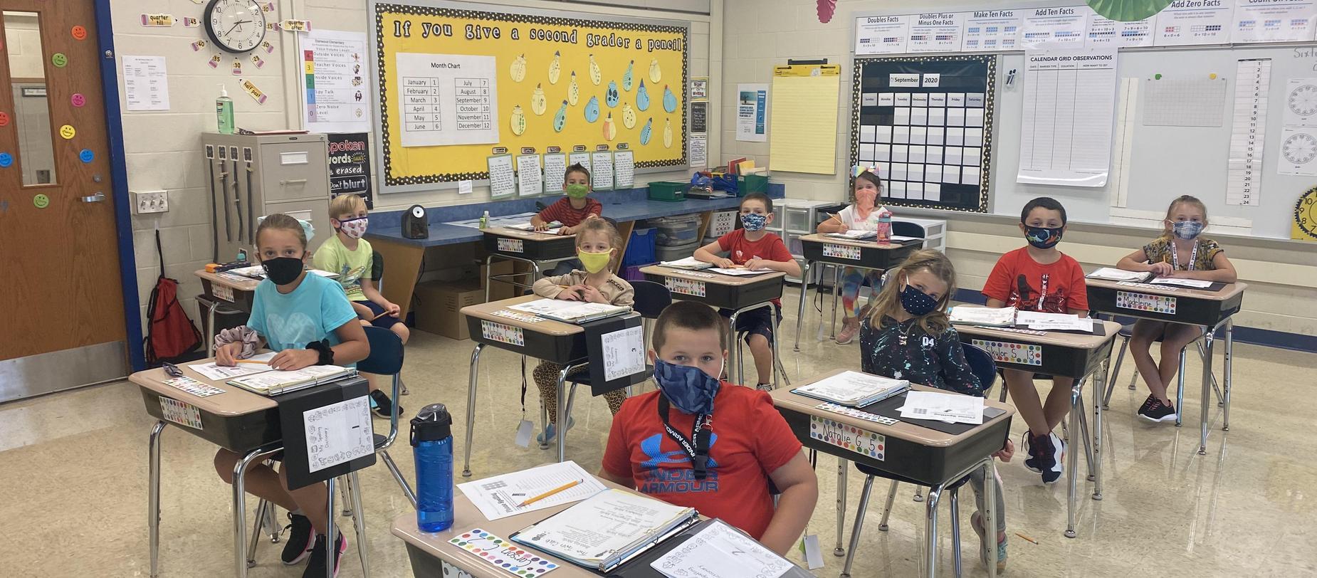 students sitting at desks wearing masks