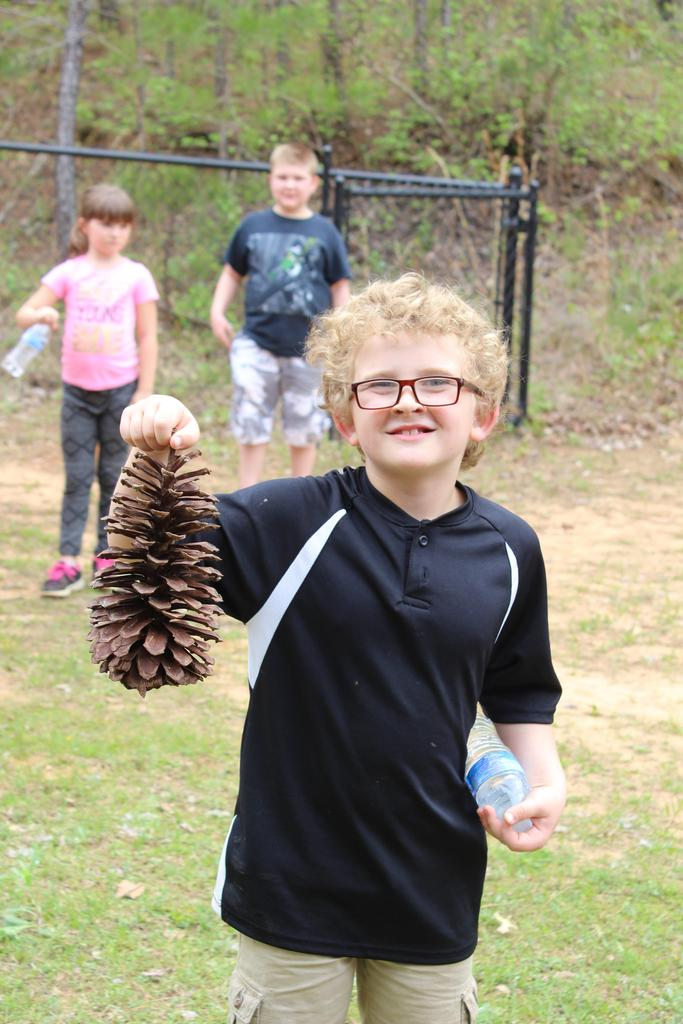 student with large pinecone