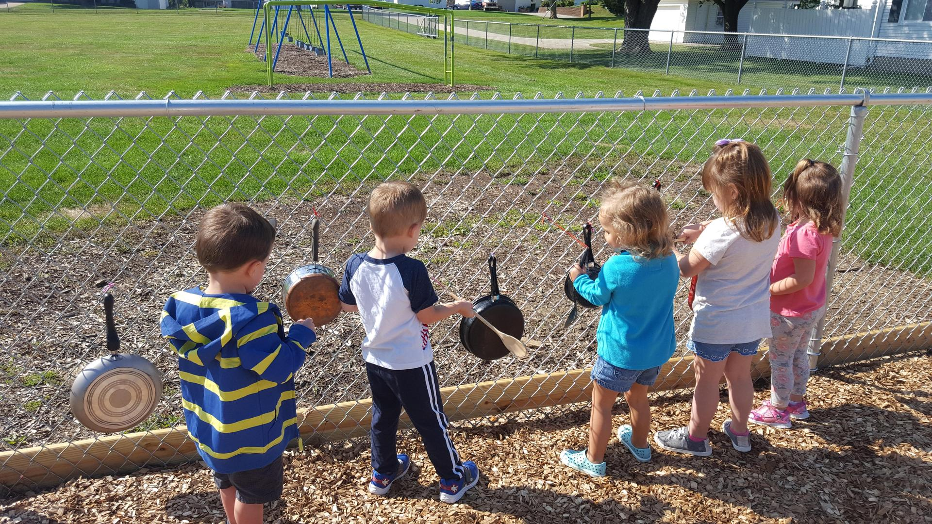 Preschool students using spoons to knock onpots and skillets suspended from chain link fence.