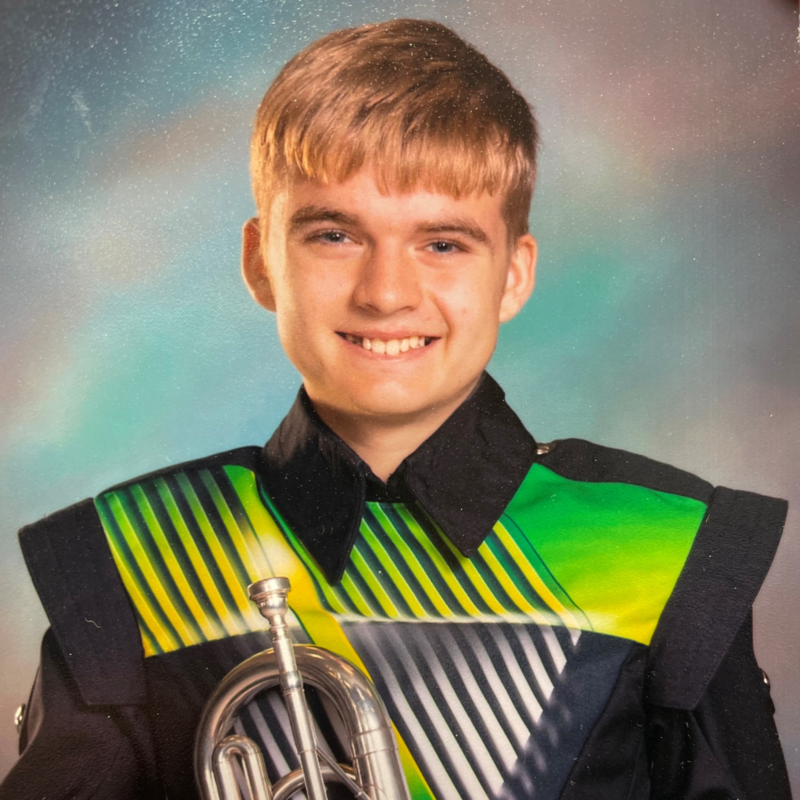 teen boy in band uniform holding his instrument