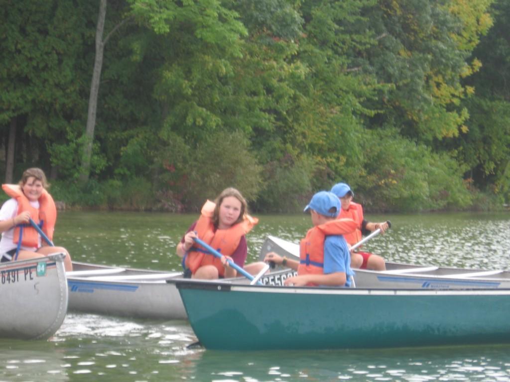 kids rowing boat at camp