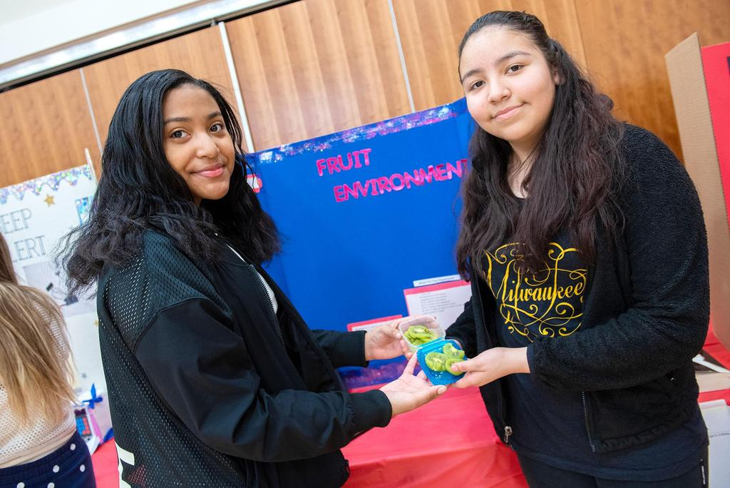 Two students old some of the materials they used for their project