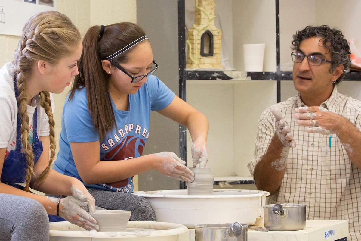 Clay teacher teaching pottery wheel with two students - Comprehensive visual arts