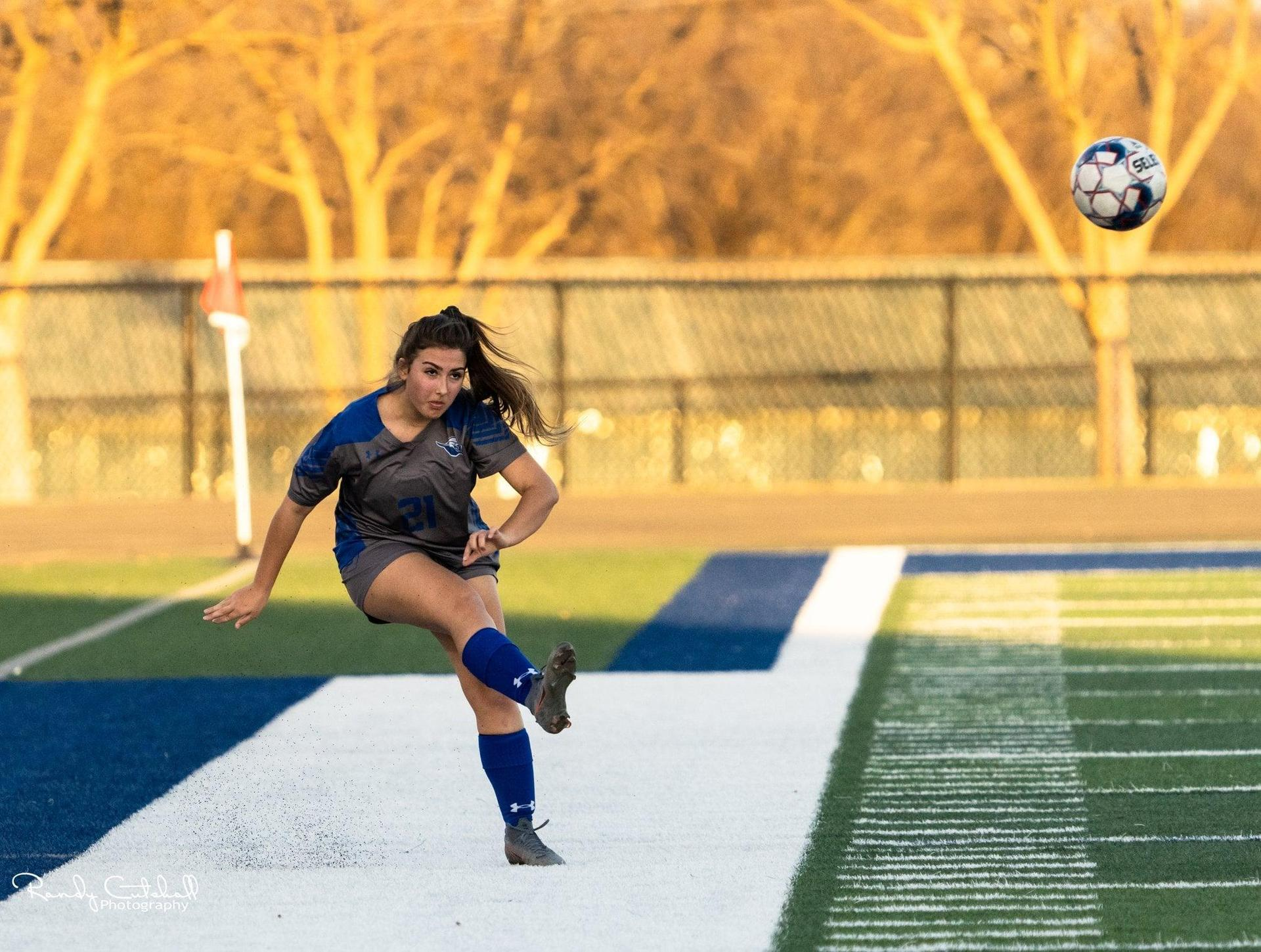 Lady Roos Soccer Player Kicking the Ball
