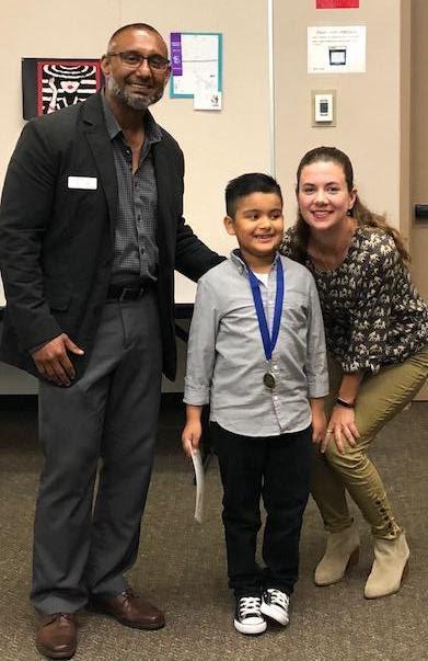 student posing with Principal and Vice Principal