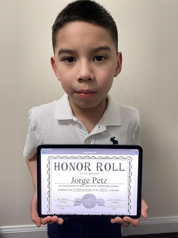 Jorge holding honor roll certificate