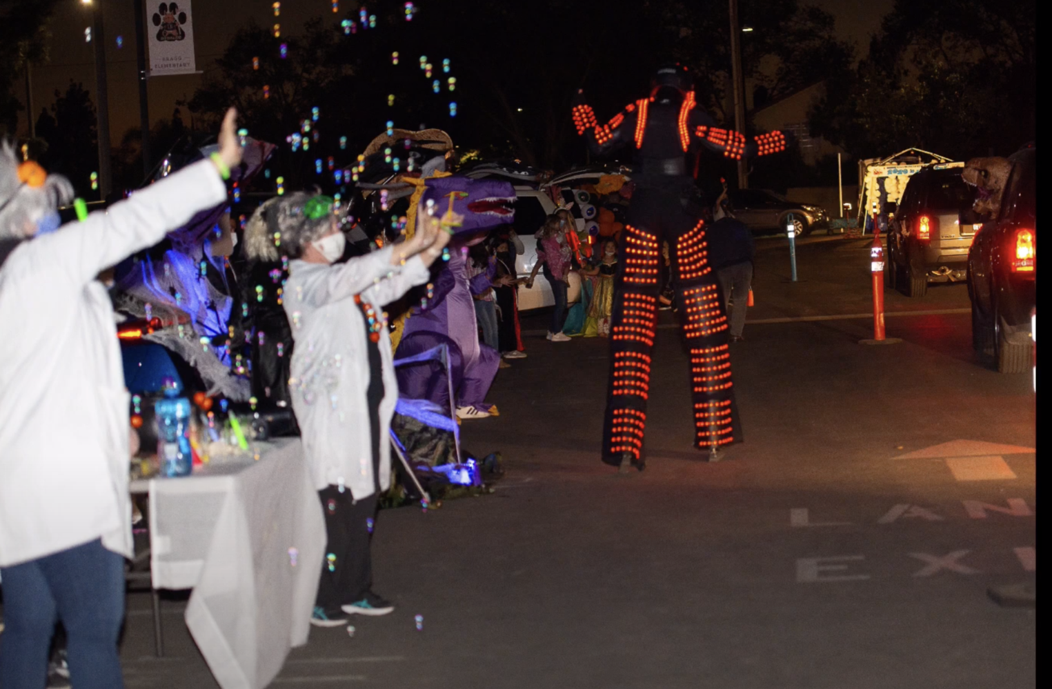 people in costume waving by to passing cars