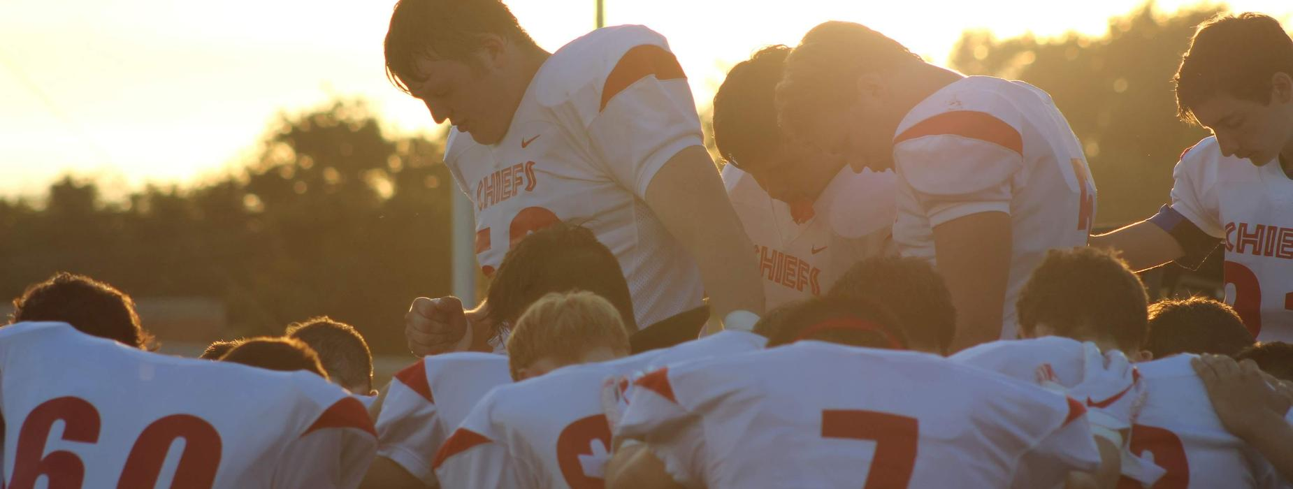 Football players huddling in prayer before a game