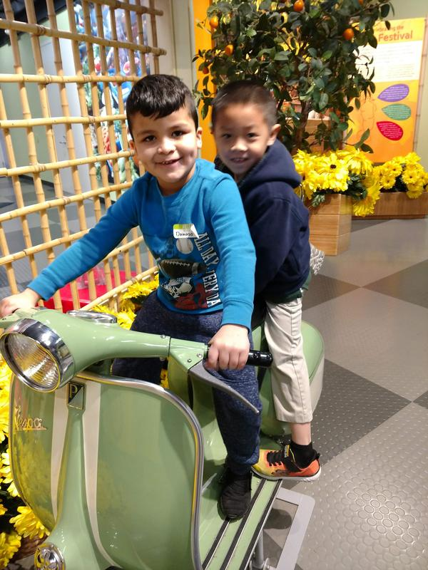 Two students pose on a motorbike exhibit
