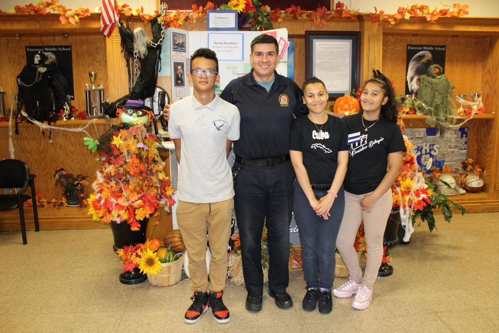 Felix De Garcia with three Students in front of the entryway