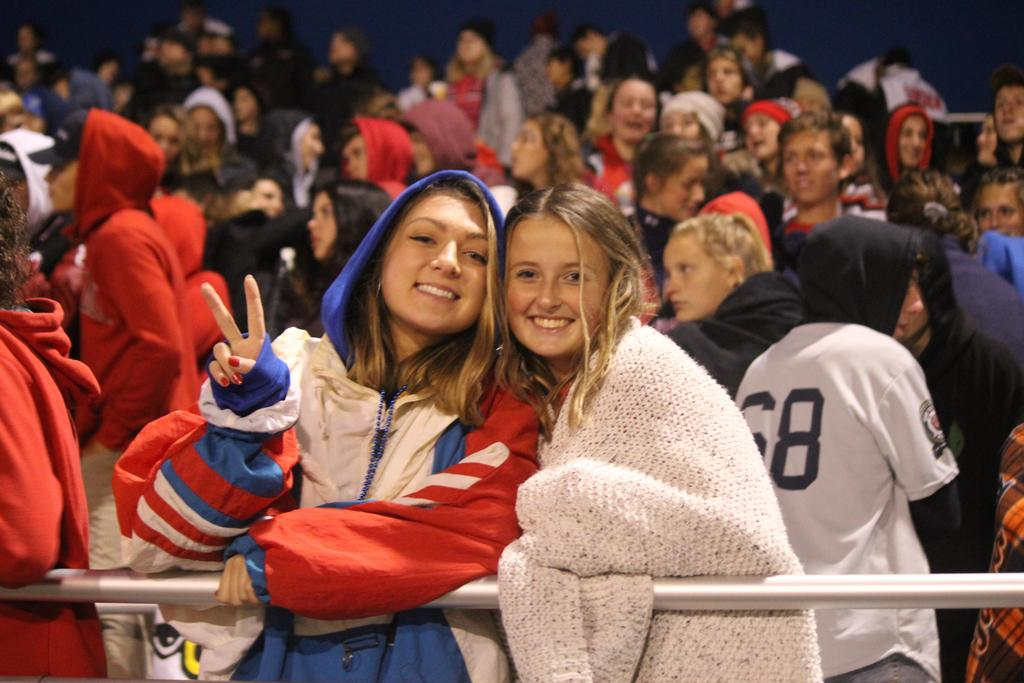 Two girls bundled up at a cold football game