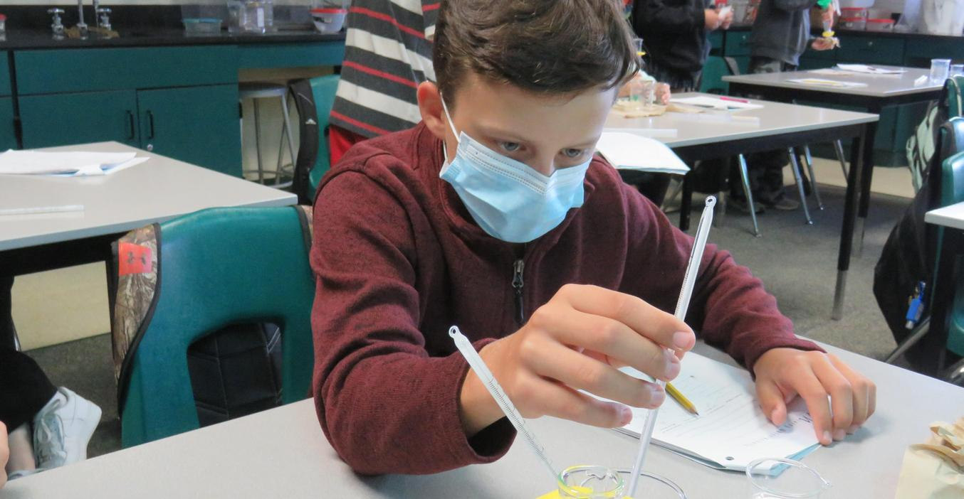 A student takes a temperature reading during an experiment.