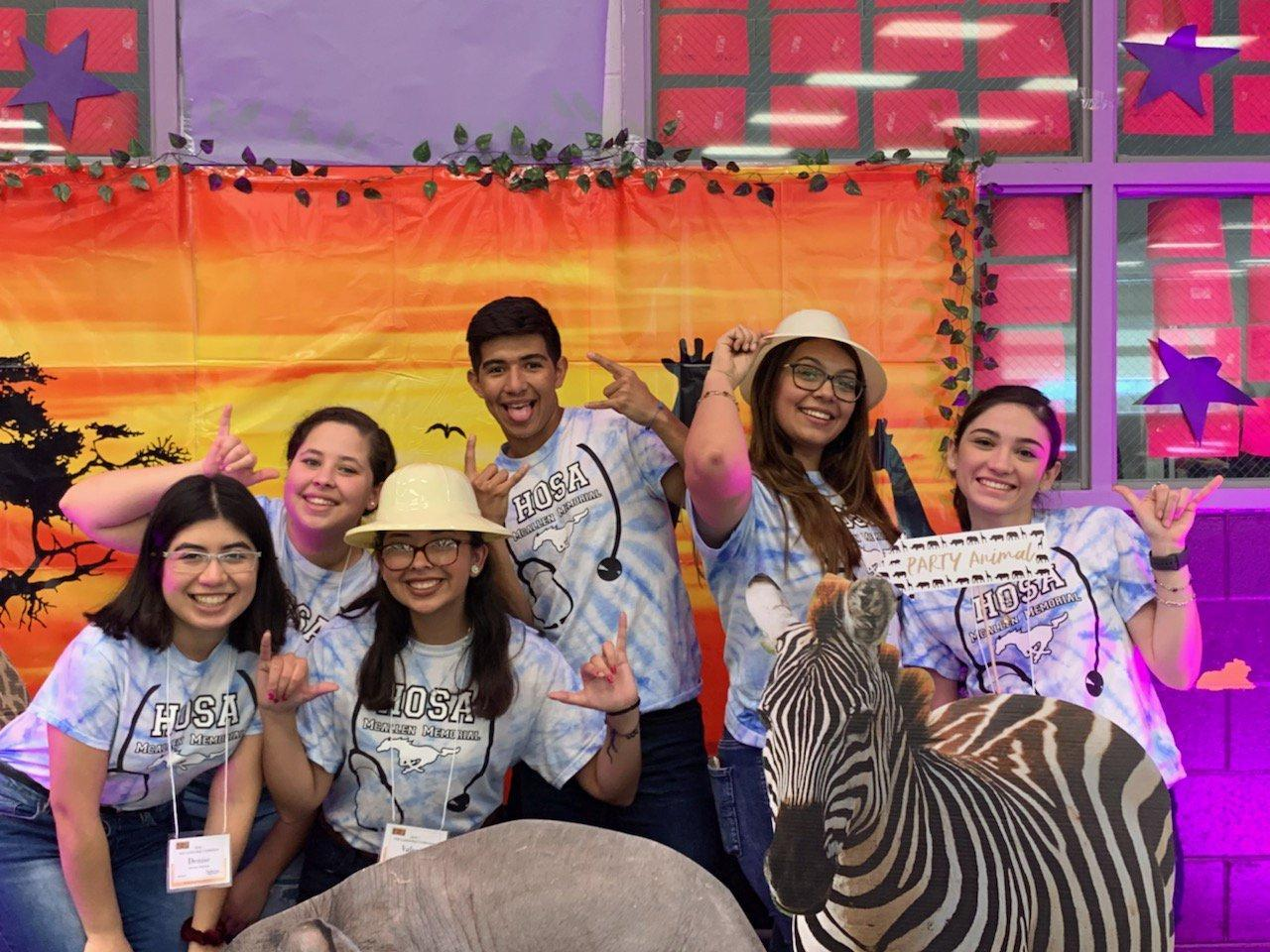 students posing with mustang hand symbol in front of safari themed background