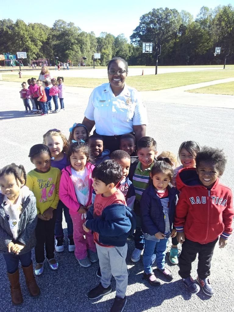 Fire and Life Safety Educator poses with students.