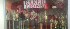 Baker's trophy case with pom poms, a football, basketball, jerseys, and trophies
