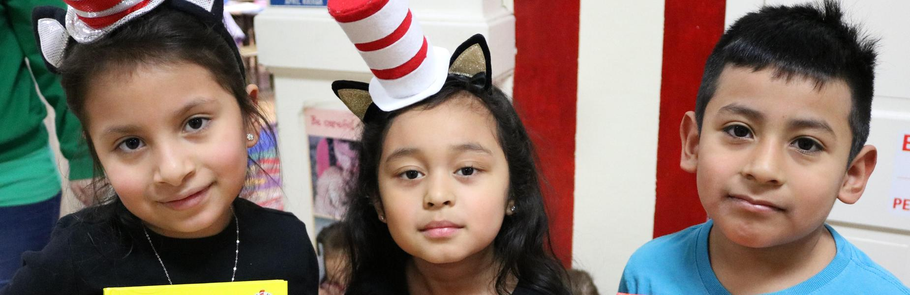 Photo of three 2nd graders wearing Cat in the Hat hats during Read Across America Day.