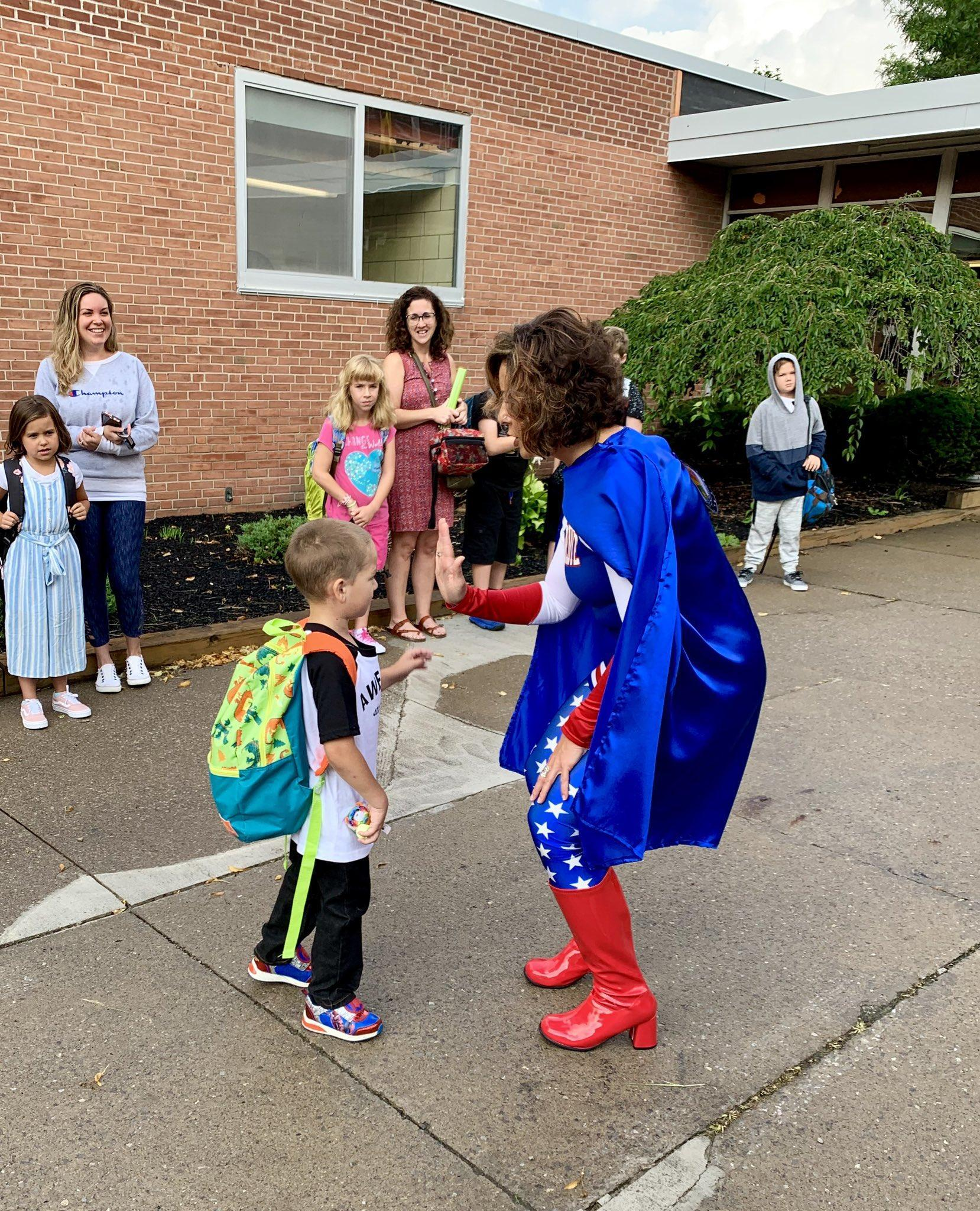Mrs. Wright, the elementary principal, dressed in a superhero costume, gives a high five to a kindergarten student outside of the school building as he comes to school for the first time.  Other parents and students are smiling and watching.