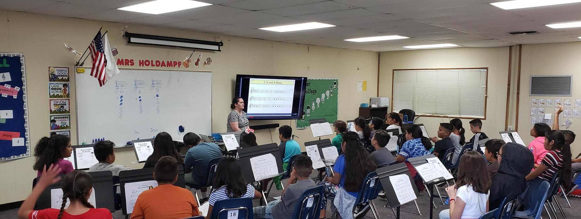 students learning music from their teacher