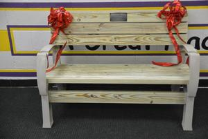 A wooden bench with red bows on the ends.