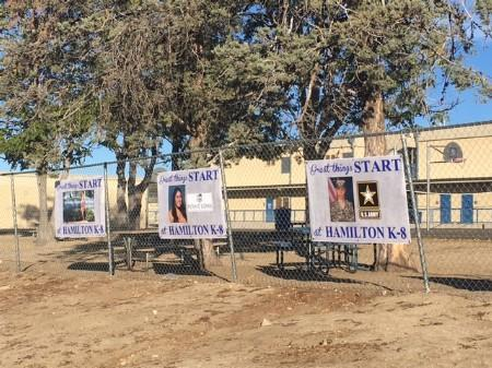 Banners of prior students who are currently attending college/military hanging on fence