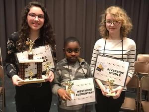 Winner, runner up and 3rd place Columbia County School District Spelling Bee winners holding trophies and certificates