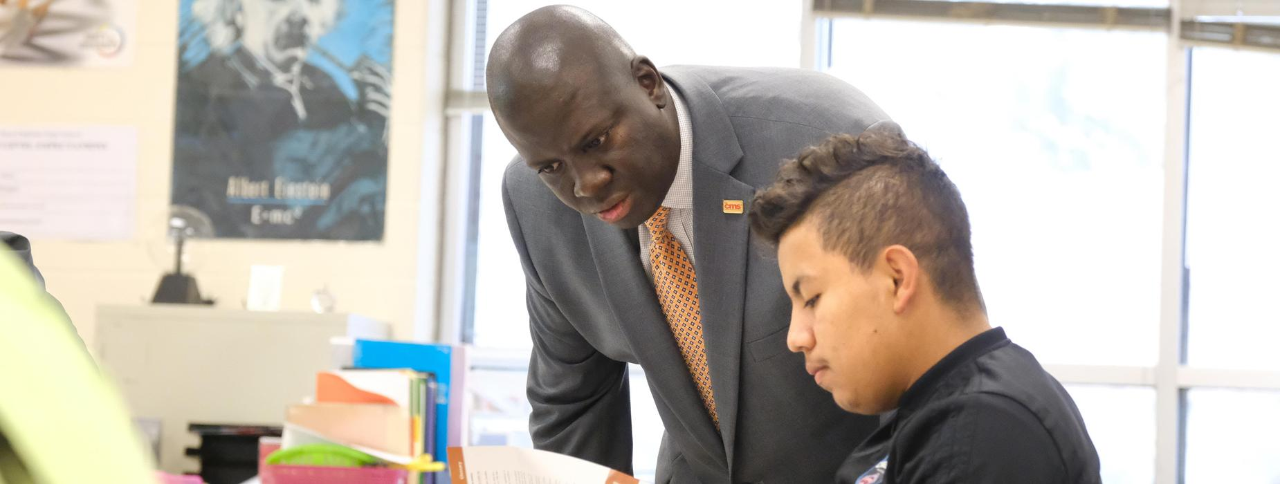 Superintendent Earnest Winston assists a student.