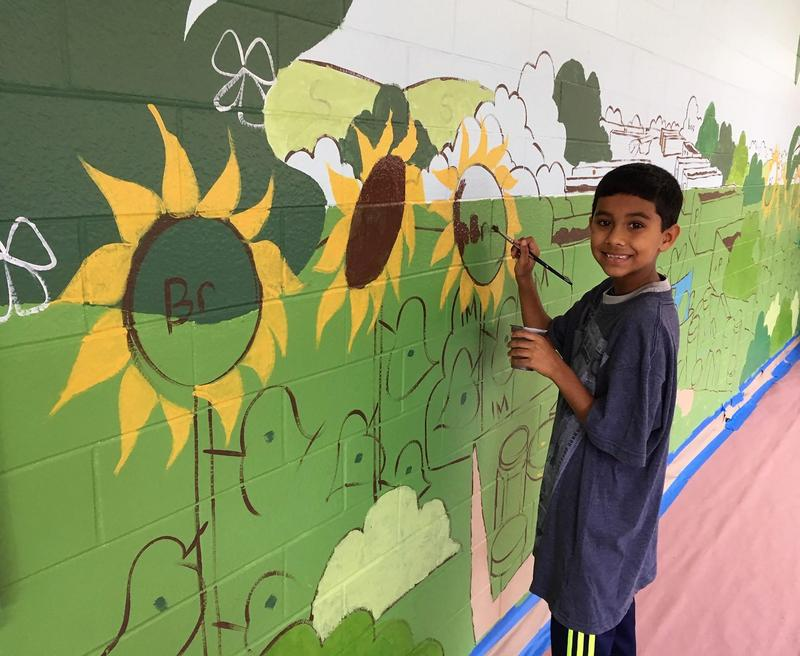 Jefferson second grader joins schoolmates and parent volunteers last month in painting colorful murals in school hallways.