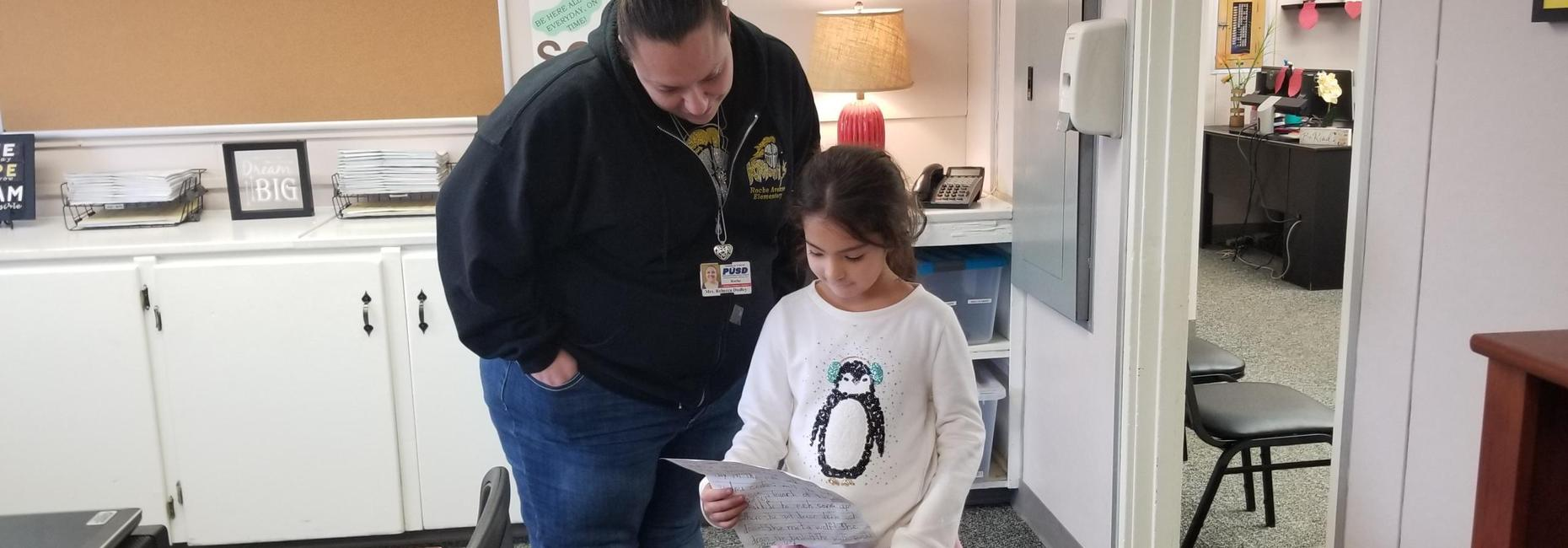 1st Grade student reading her story to Mrs. Dudley