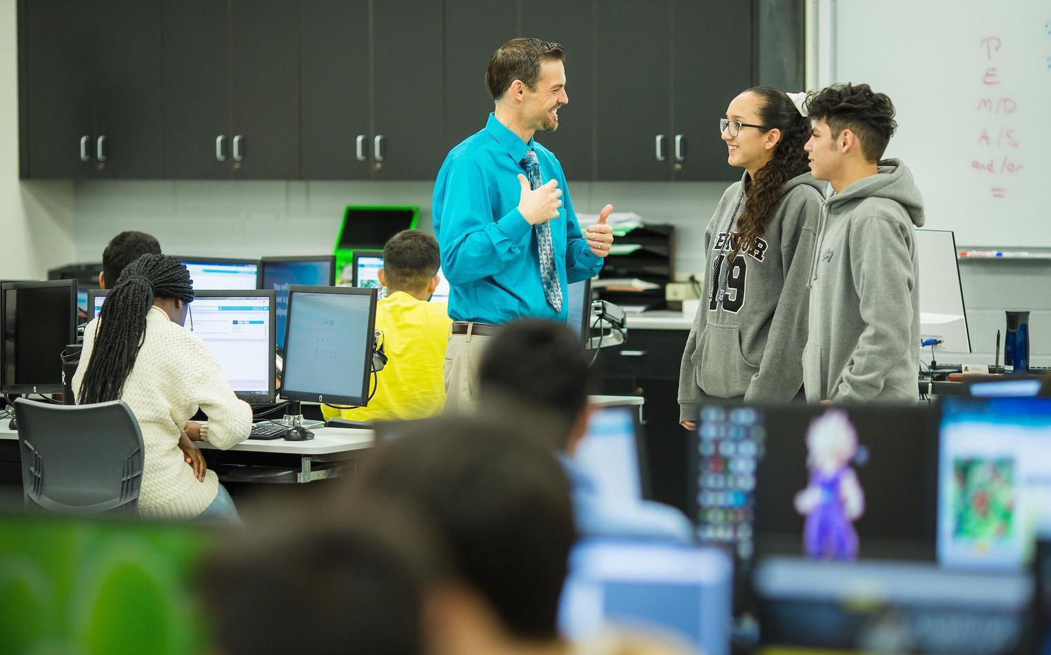 Computer science teacher talking with students.